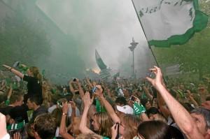 Jubelnde Fans im grünen Rauch während der Aufstiegsfeier vor dem Rathaus, endlich kann das »Un« aus »Die Unaufsteigbaren« gestrichen werden. (Foto: Alexander Mayer)