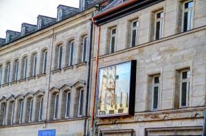 Die neuen Fenster fügen sich nicht unbedingt harmonisch in das historische Fassadenbild ein, hier spiegelt sich der Kran gegenüber (Foto: Alexander Mayer)
